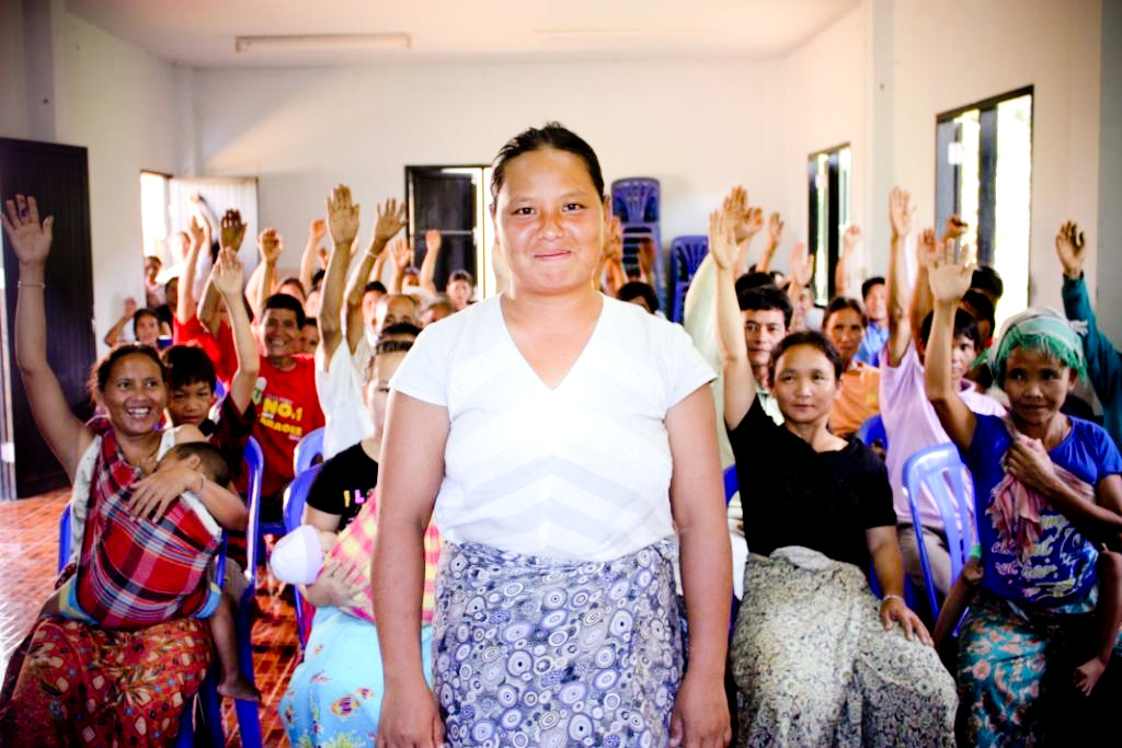 One of IJM's clients stands proudly before her neighbours and family, gathered for a 'community guarantee meeting', where other members of her village vouch that she is member their community.
