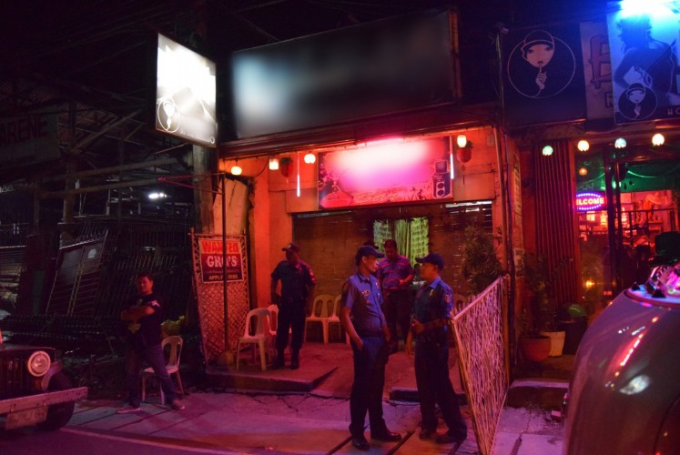 Police stand watch outside the karaoke bar where young women were rescued from trafficking